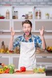 Gillende mens die diner in keuken proberen te koken Stock Fotografie