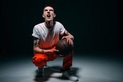 Gillende mens in eenvormige gevangenis en manchetten die basketbalbal houden royalty-vrije stock afbeelding