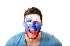 Gillende mens met de vlag van Slovenië op gezicht Stock Foto