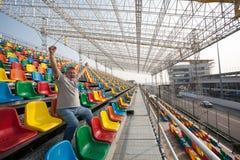 Gillende mens met handen omhoog in de zetels voor toeschouwers Stock Foto