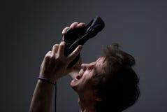 Gillende mens met hoofdtelefoons. Een ventilator van rots Royalty-vrije Stock Afbeeldingen