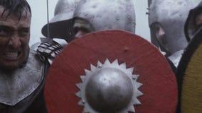 Gillende middeleeuwse militairen in de hitte van de slag stock videobeelden