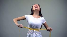Gillende vrouw die metend band, sterke wens, probleem slank te zijn aanhalen stock afbeelding