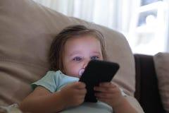 Gilr младенца играя игры по телефону стоковые изображения rf