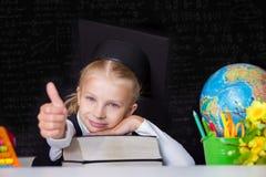 Gilr in cappuccio di graduazione che mostra segno giusto Fotografia Stock
