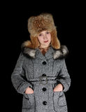 Gilr in coat and fox cap  on black background Stock Photography