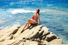 Gilr, das auf der Klippe nahe bei blauem Meer sitzt Lizenzfreie Stockbilder
