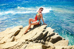 Gilr, das auf der Klippe nahe bei blauem Meer sitzt Lizenzfreie Stockfotos