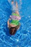 Gilr de los niños que nada bajo el agua en piscina azul Imagen de archivo