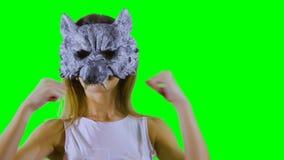 Gilr die de krassen van het wolfsmasker dragen bij groene achtergrond stock videobeelden