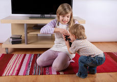 Gilr fighting with her toddler brother over the remote control Stock Photography