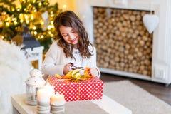 Gilr moreno delante del piel-árbol y chimenea con las velas y los regalos Una muchacha que envuelve un presente Año Nuevo Navidad imagenes de archivo