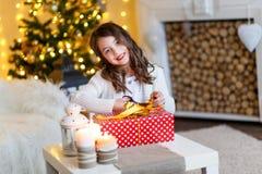 Gilr moreno delante del piel-árbol y chimenea con las velas y los regalos Una muchacha que envuelve un presente Año Nuevo Navidad fotografía de archivo