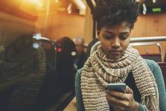 Gilr negro en el coche del tren con smartphone Imagen de archivo