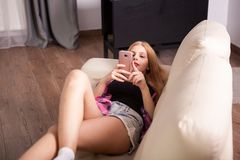 Gilr in short jeans lying on the sofa. With a phone in hands Royalty Free Stock Images
