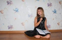 Gilr siedzi na podłoga z notatnikiem w rękach Zdjęcie Royalty Free