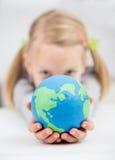 Gilrl que sostiene el globo de la tierra Imágenes de archivo libres de regalías