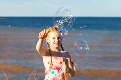 Gilrl with soap bubbles on seashore Stock Photos