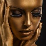 Gilt. Den guld- kvinnan vänder mot closeupen. Futuristic Giled smink. Målat flå Arkivbilder