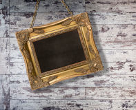 Gilt Frame. Hanging with chain on grungy wooden background stock photos