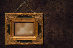 Gilt Frame On Wall. Gilt wooden frame hanging from chain on wall Stock Photo