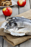 Gilt-head bream fishes in wicker basket. On wooden table Royalty Free Stock Image