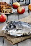 Gilt-head bream fishes in wicker basket. On wooden table Stock Images