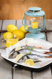 Gilt-head bream fishes in wicker basket. On wooden table. Lantern and juicy lemons in the background Stock Photo