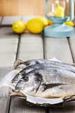 Gilt-head bream fishes in wicker basket. On wooden table. Lanterns and juicy lemons in the background Royalty Free Stock Photos