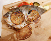 Gilt-head bream roasted in paper with vegetables Stock Image