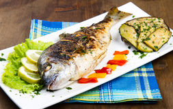 Gilt head sea bream on plate with lemon ,salad and grill Stock Photo