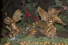 Gilt little angels on stall roof at Xmas market time Stock Photo
