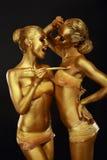 Gilt. Två roliga kvinnor med målarpenseln. Futuristiskt glansigt guld- smink arkivbilder