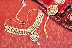 Giltter halsband av den indiska bruden på den röda bakgrunden royaltyfri foto