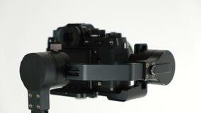 Gimbal met digitale camera roteert op witte achtergrond stock footage