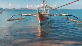Gimbal schot van traditionele Filipijnse die bangkaboten op schitterend tropisch strand worden verankerd reis concept Het eiland  stock footage