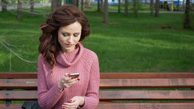 Gimbal shot of female teen girl talking on the phone sitting on bench in spring sunny day, uhd prores footage stock video footage
