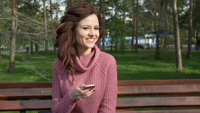 Gimbal shot of female teen girl talking on the phone sitting on bench in spring sunny day, uhd prores footage stock footage
