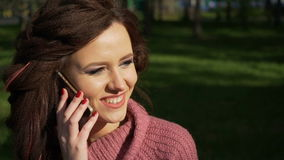 Gimbal shot of female teen girl talking on the phone sitting on bench in spring sunny day, uhd prores footage stock video