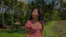 Gimbal shot on young beautiful and happy Asian Chinese woman in stylish Summer dress walking on palm trees jungle. Outdoors gimbal shot on young beautiful and stock video