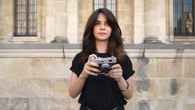 Young woman making photo rewinding a film camera on background of old buildings in Paris. Gimbal slow motion middle shot of young woman looking at the camera stock footage
