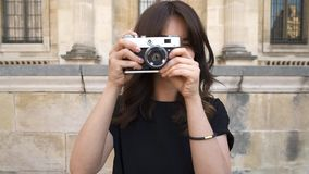 Young woman making photo rewinding a film camera on background of old European city. Gimbal slow motion middle shot of young woman looking at the camera stock video footage