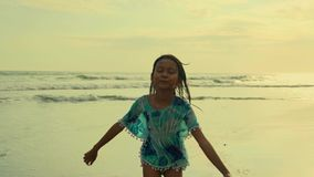 Gimbal steadycam tracking shot of 8 or 9 years old beautiful and happy Asian Indonesian child girl running carefree on the beach stock footage