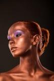 gimbals Złoty kobiety twarzy zbliżenie Futurystyczny Pozłocisty makijaż Malujący skóra brąz obraz stock