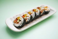 Gimbap Kimbap. Is a Korean dish made from steamed white rice bap and various other ingredients, rolled in gim sheets of dried laver seaweed and served in bite Stock Photography