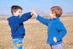 Gimme five!. Two boys playing gimme five in a sunny autumn day Stock Photos