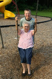 Gimme A Push. Grandson pushing his grandmother on a playground swing royalty free stock image