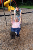 Gimme A Push 3. Teenage grandson pushing his grandmother on a playground swing royalty free stock image