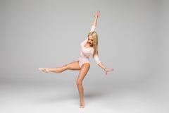 Gimnasia del bailarín de la mujer que se coloca en una pierna en el fondo blanco Fotos de archivo libres de regalías