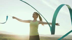 Gimnasia rítmica: La muchacha en mono del deporte realiza ejercicio de la gimnasia con una cinta azul en al aire libre en la pues almacen de video